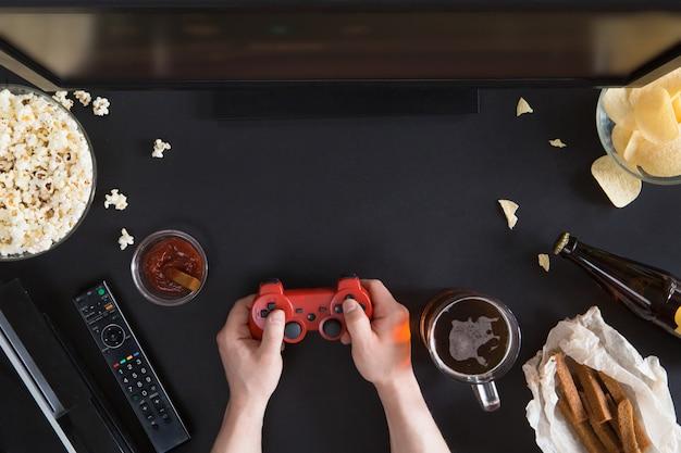 黒の背景、ゲーマーコンセプトにスナックとラップトップで不健康な食品のトップビュー Premium写真