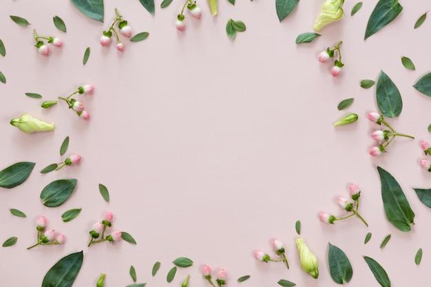 ピンクの背景に分離された葉とコピースペースを持つ丸い花のフレームの平面図を置く。グリーティングカードの概念 Premium写真