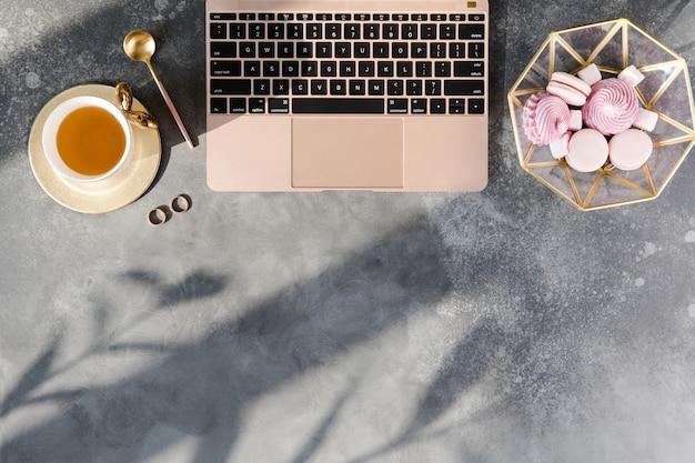Домашний офис современный чердак стол. рабочая область с пастельным розовым блокнотом, чаем и украшениями на сером фоне Premium Фотографии