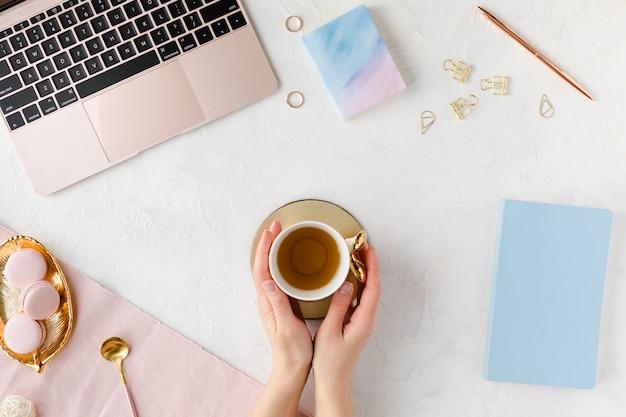 コンピューターのキーボード、ノート、ピンクの牡丹の花の花束、携帯電話、フラットレイアウトと女性ビジネス職場の上からの眺め。 Premium写真