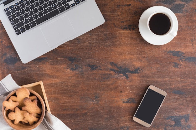 クリスマスのモミの木の枝、ジンジャーブレッドマン、コーヒーカップ、木製のコンピューターまたはラップトップのキーボードのフラットレイアウト。 Premium写真