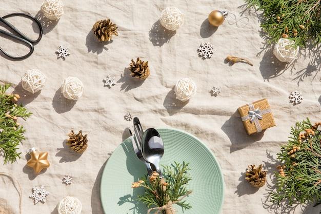 クリスマステーブルの設定。ビンテージのテーブルクロスにプレートとカトラリー、金の装飾、松ぼっくりのクリスマスの休日の装飾 Premium写真