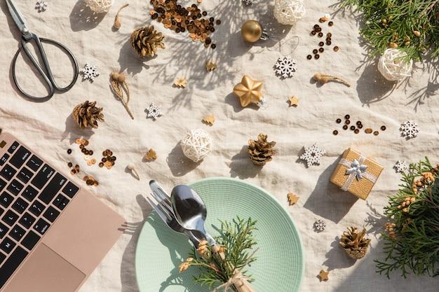 Рождественские украшения. праздничная тарелка и столовые приборы, ноутбук с рождественские украшения в солнечный день. праздник, новый год, жесткий свет с тенями Premium Фотографии