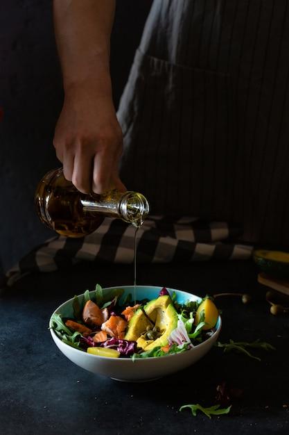 アボカドとサーモンのグリルのサラダを準備する男 Premium写真