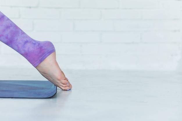 Крупный план на ногах в спортивных леггинсах женщины занимаются йогой Premium Фотографии