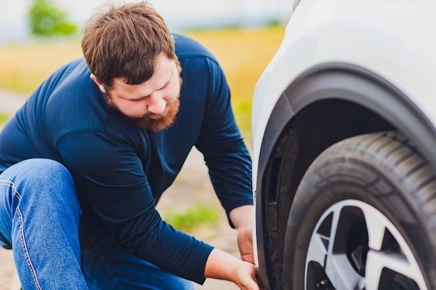 壊れた車の隣の道路に立っている間、髪を引っ張ってストレスとイライラのドライバー。ロードトリップの問題と支援の概念。煙。 Premium写真