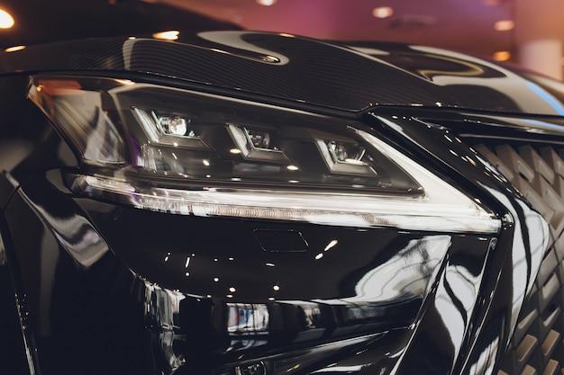 車の白い体のクローズアップのヘッドライトをクローズアップ Premium写真