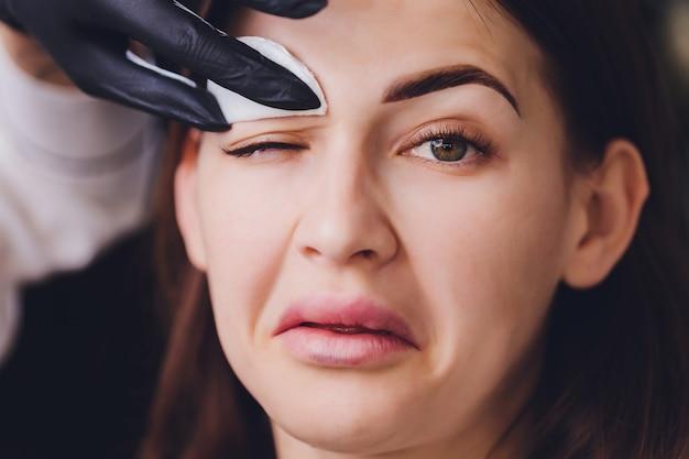 クライアントの眉毛から塗料を除去する美容師 Premium写真