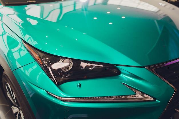 車のターコイズブルーのボディのクローズアップのヘッドライトをクローズアップ。 Premium写真