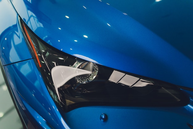 車の青い体のクローズアップのヘッドライトをクローズアップ。 Premium写真