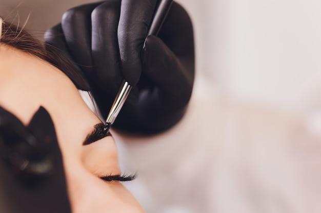 美容師-メイクアップアーティストは、セッション修正で以前に摘み取ったデザインのトリミングされた眉にペイントヘナを適用します。顔の専門的なケア。 Premium写真