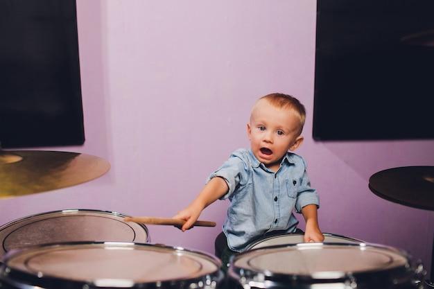 小さな男の子はレコーディングスタジオでドラムを演奏します。 Premium写真