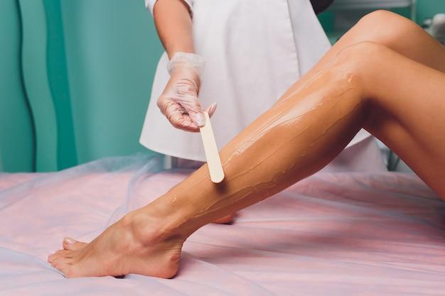 Косметолог готовится к депиляции и наносит крем с восковой палочкой на красивые женские ножки. салон красоты. Premium Фотографии