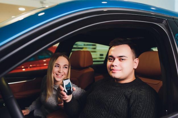 ディーラーのハンサムな男と一緒に車を選ぶ彼の愛情のあるガールフレンドで一緒に新しい車に座って美しい愛情のあるカップル Premium写真
