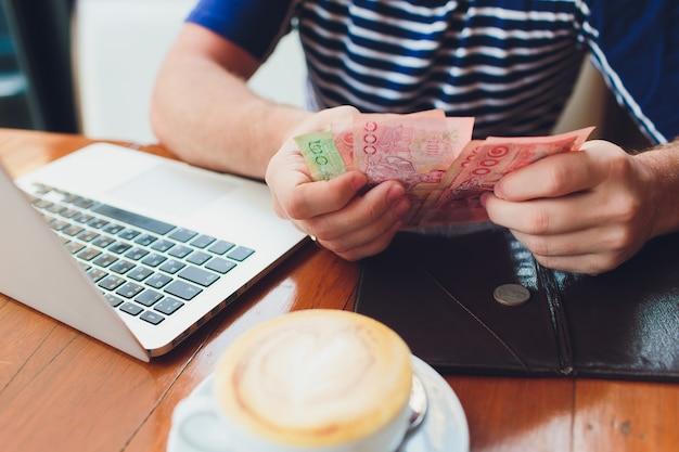 カフェで法案を払って男。彼はお金を入れます。レストランで昼食を食べている忙しい人。サービスのコンセプト。 Premium写真