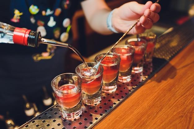 Бармен человек делает горячие алкогольные снимки на баре в пабе с профессиональной горелкой. бармен зажигает зажигалку над стаканом. отдых в ночном клубе. горячие огненные напитки. позволяет вечеринка. Premium Фотографии