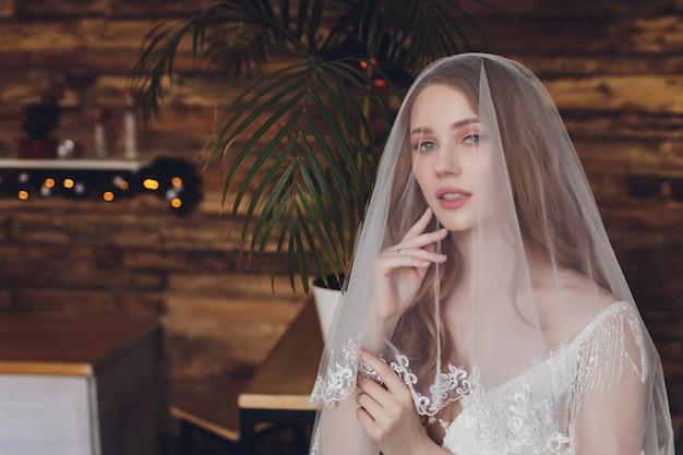 Красивая женщина позирует в свадебном платье. Premium Фотографии