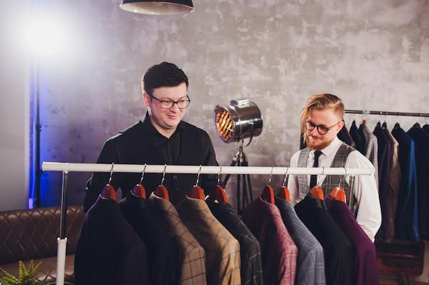 Продавец помогает мужчине выбрать куртку Premium Фотографии