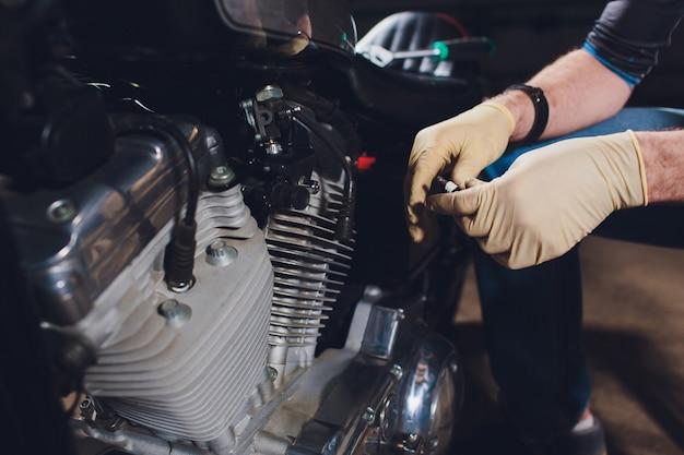 男は自転車を修正します。自信を持って若い男が彼のガレージ近くのバイクを修理します。 Premium写真