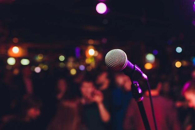 Микрофон с запачканным красочным ярким светом в темной предпосылке ночи, мягком изображении фокуса для концепций связи технологии дела. Premium Фотографии