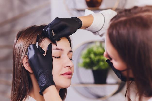 美容師-メイクアップアーティストは、セッション修正で以前に摘み取ったデザインのトリミングされた眉毛にペイントヘナを適用します。顔の専門的なケア。 Premium写真