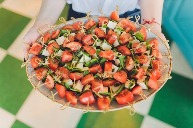 スナックカナッペ揚げパントマトパセリとサラミを提供するクローズアップの大皿。 Premium写真