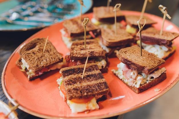 チキンビーコンハム、エッグサラダコールドカットブリオッシュサンドイッチ、ケータリング、セミナー、コーヒーブレーク、朝食、ランチ、ディナー、ビュッフェ、ミーティンググループ用のミニクラブサンドイッチ。 Premium写真