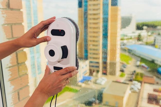 屋外の高層ビルの窓を掃除する掃除機ロボット。 Premium写真