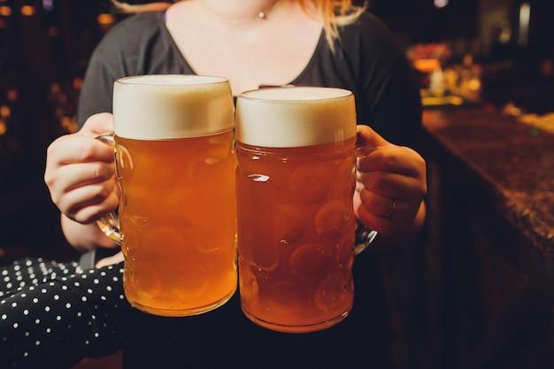 トレイに冷たいビールのグラスを提供するウェイター。 Premium写真