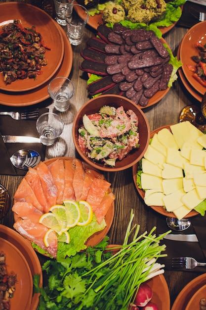 Богато накрыты столовые блюда грузинской кухни, множество вкусных блюд, вина, фрукты и жареное мясо. Premium Фотографии