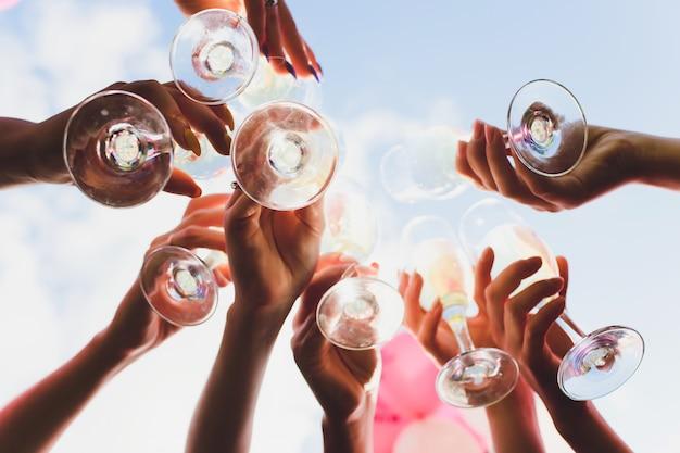 アルコールと乾杯、パーティーで素晴らしく眼鏡。イベントおめでとうございます。陽気なパーティーの友達。 Premium写真