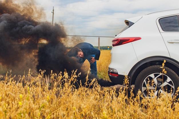 壊れた車の隣の道路に立っている間、髪を引っ張ってストレスとイライラしたドライバー。ロードトリップの問題と支援の概念。煙。 Premium写真