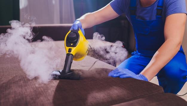 Работник химчистки, удаление грязи из мебели в квартире, крупным планом. Premium Фотографии