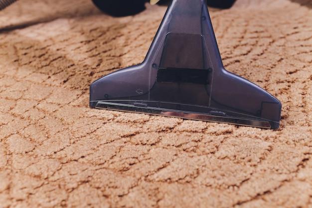 自宅でカーペットを掃除する掃除機のノズルのクローズアップ。 Premium写真