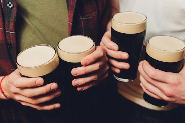 レンガの壁に暗いビールと軽いビールのグラスをチリンと男性グループ Premium写真