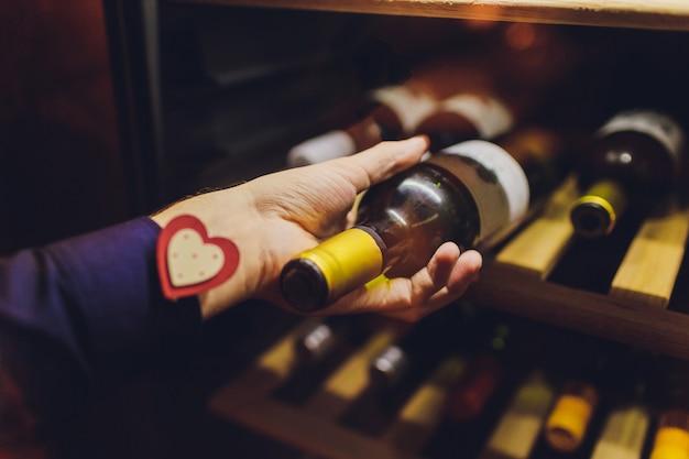 店のラックの近くにワインのボトルとソムリエ。 Premium写真