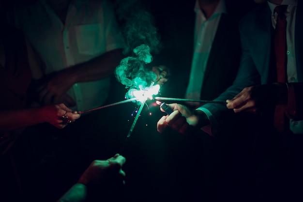 Праздник фон с бенгальскими огнями. молодые друзья держа света бенгалии, крупный план, селективный фокус. день рождения или праздник зимних праздников Premium Фотографии