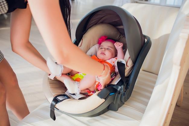 Семья, транспорт, безопасность, путешествие на автомобиле и люди концепции - счастливая мать фиксирует девочку в детском кресле у себя дома Premium Фотографии