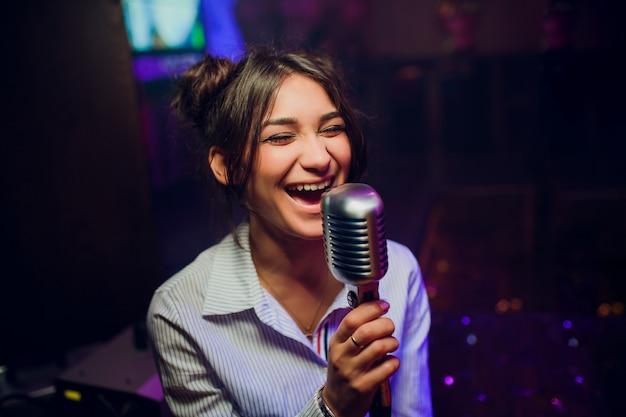 美しいぼやけた色ボケに対して歌うためのモダンなマイク。 Premium写真