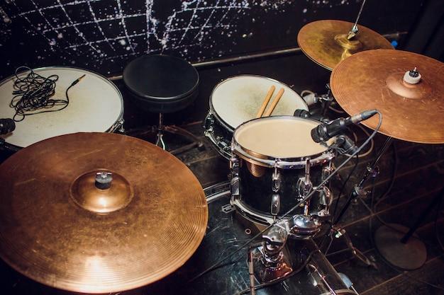 Живая музыка в старинном стиле, барабанщик играет с барабанными палочками на рок-барабане Premium Фотографии