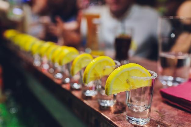 バーテンダーが強いアルコール飲料をバーの小さなグラスに注いでいます。 Premium写真