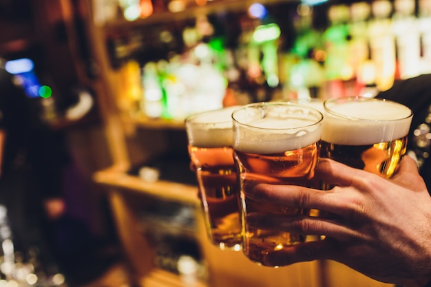 Бармен руки разлива пива лагер в стакан. Premium Фотографии