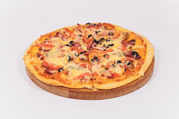 白で隔離される木製のスタンドにシーフードのおいしいピザ。 Premium写真