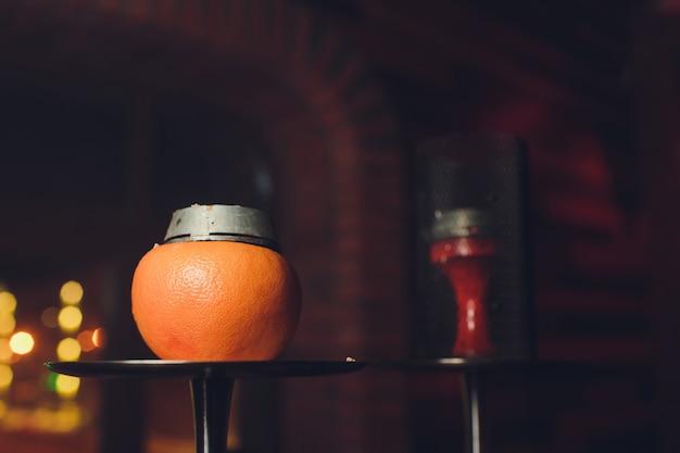 オレンジ色の高級水ギセル。フルーツのエキゾチックなボウル。水ギセルラウンジ。 Premium写真