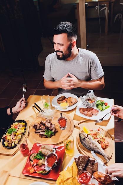 Человек за большим столом с едой. Premium Фотографии