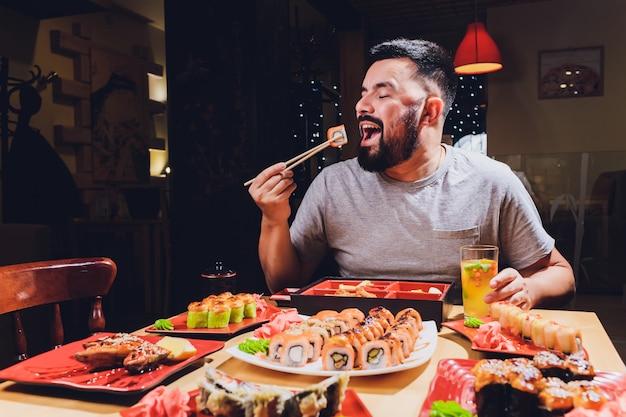 Туристический человек ест азиатскую еду уличное кафе, улыбка с помощью палочек. Premium Фотографии
