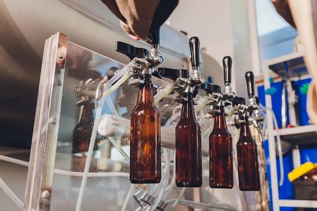 ビール醸造所の工場で、コンベアラインのガラス瓶にビールをこぼします。産業労働、食品および飲料の自動生産。工場での技術的作業。 Premium写真