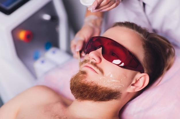 マスター医師は、レーザーでひげを生やした男性の永久に不要な顔の毛を除去する手順を実行します。美しさと健康。 Premium写真