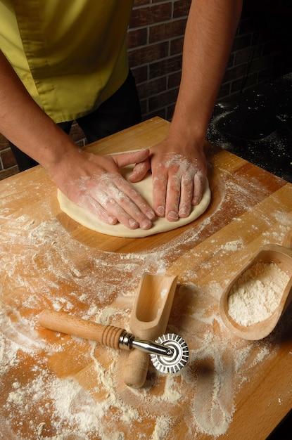シェフはフェットチーニ、スープ、ピザの生地を準備します Premium写真