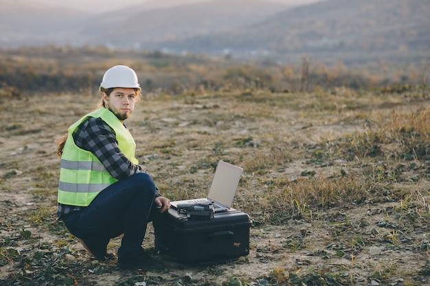 ハード帽子の産業エンジニアは、タッチスクリーンのラップトップを使用しています。彼は重工業工場で働いています。 Premium写真